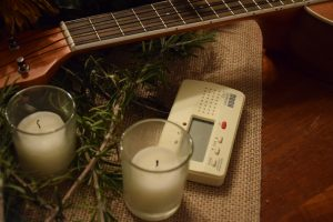 Candles, guitar, metronome and pine boughs